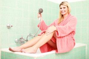 Frau im Bademantel mit Duschkopf